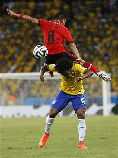Mexico's Marco Fabian (8) flips over Brazil's Willian while trying to head the ball during the group A World Cup soccer match between Brazil and Mexico at the Arena Castelao in Fortaleza, Brazil, Tuesday, June 17, 2014. (AP Photo/Eduardo Verdugo)