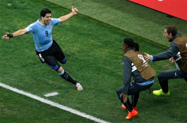 Uruguay's Luis Suarez, left, celebrates scoring the opening goal during the group D World Cup soccer match between Uruguay and England at the Itaquerao Stadium in Sao Paulo, Brazil, Thursday, June 19, 2014. (AP Photo/Michael Sohn)