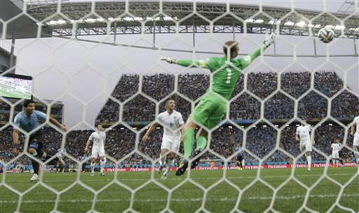Uruguay's Luis Suarez, left, scores the opening goal past England's goalkeeper Joe Hart, center, during the group D World Cup soccer match between Uruguay and England at the Itaquerao Stadium in Sao Paulo, Brazil, Thursday, June 19, 2014. (AP Photo/Kirsty Wigglesworth)