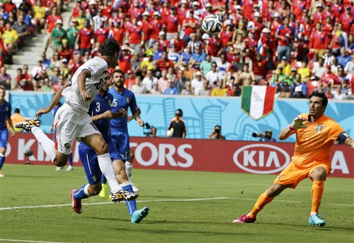 Costa Rica's Bryan Ruiz, left, heads the ball at Italy's goalkeeper Gianluigi Buffon to score his side's first goal during the group D World Cup soccer match between Italy and Costa Rica at the Arena Pernambuco in Recife, Brazil, Friday, June 20, 2014. (AP Photo/Ricardo Mazalan)