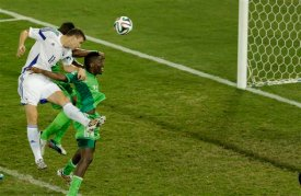 Bosnia's Edin Dzeko, left, heads a ball during the group F World Cup soccer match between Nigeria and Bosnia at the Arena Pantanal in Cuiaba, Brazil, Saturday, June 21, 2014. (AP Photo/Fernando Llano)