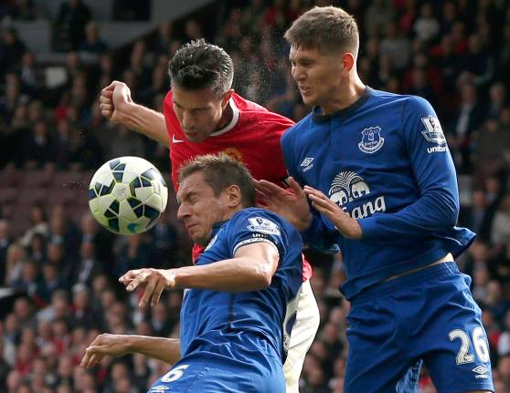 Manchester United's Van Persie challenges Everton's Jagielka and Stones during their English Premier League soccer match at Old Trafford in Manchester